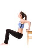 Junge Frau, die einige Übungen unter Verwendung des Stuhls tut Stockfotos