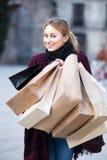 Junge Frau, die EinkaufsPapiertüten anhält Lizenzfreies Stockfoto