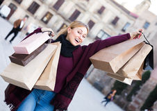 Junge Frau, die EinkaufsPapiertüten anhält Stockfoto