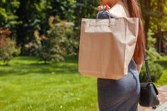 Junge Frau, die Einkaufspapiert?ten im Sommerpark h?lt und modische Ausstattung tr?gt stockfotografie