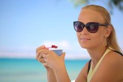 Junge Frau, die Eiscreme auf dem Strand isst Stockbilder