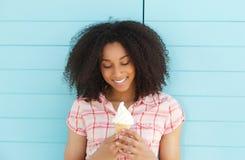 Junge Frau, die Eiscreme lächelt und schaut Lizenzfreie Stockfotos