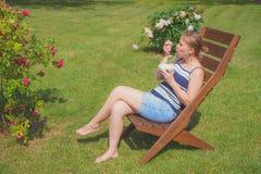 Junge Frau, die Eiscreme sich entspannt und isst Stockbilder