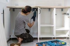 Junge Frau, die Elektroschrauber zur Installation verwendet stockfotografie