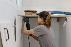 Junge Frau, die Elektroschrauber zur Installation verwendet lizenzfreie stockfotos