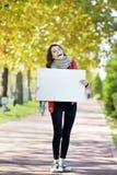 Junge Frau, die empyt Anschlagtafel hält Stockbilder