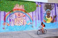 Junge Frau, die entlang bunte Wand in Montevideo, Uruguay radfährt stockbild