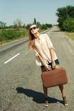 Junge Frau, die entlang einer Straße trampt. Stockfoto