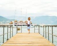 Junge Frau, die entlang Pier geht Stockbilder