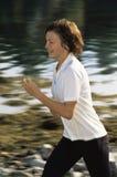 Junge Frau, die entlang Rand des Wassers läuft Stockfoto