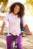 Junge Frau, die entlang Straße radfährt, um zu arbeiten Lizenzfreie Stockbilder