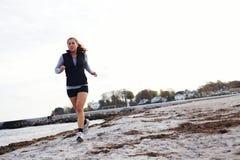 Junge Frau, die entlang Strand rüttelt Stockfotos
