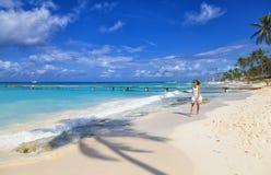 Junge Frau, die entlang tropischen Strand des weißen Sandes geht lizenzfreies stockfoto