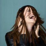 Junge Frau, die entlang zur Musik singt Lizenzfreie Stockbilder