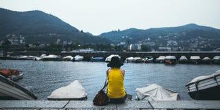 Junge Frau, die entspannt durch den See während der Sonnenuntergangzeit sitzt stockfoto