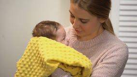 Junge Frau, die entzückendes neugeborenes Baby, liebende Familie für angenommenes Kind streichelt stock footage