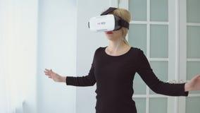 Junge Frau, die Erfahrung unter Verwendung der VR-Kopfhörergläser virtueller Realität erhält stock footage