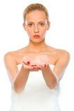 Junge Frau, die etwas auf leeren Händen darstellt Lizenzfreies Stockfoto