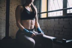 Junge Frau, die etwas Rest nach hartem Training in der Turnhalle hat Stockbilder