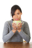 Junge Frau, die etwas vom großen Becher trinkt Lizenzfreie Stockfotos