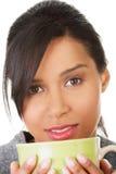 Junge Frau, die etwas vom großen Becher trinkt Lizenzfreies Stockbild