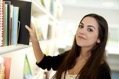 Junge Frau, die für Buch erreicht Stockfotografie