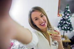 Junge Frau, die für ein Weihnachten-selfie aufwirft Junge lächelnde Frau im Weihnachtshut, der selfie Foto mit Sekt macht Lizenzfreies Stockbild