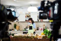 Junge Frau, die für eine kochende Show sich vorbereitet stockfotos