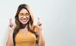 Junge Frau, die für gutes Glück wünscht Lizenzfreie Stockfotos