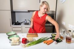 Junge Frau, die für Spargel erreicht und Messer in anderem ha hält Stockfotografie