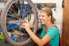 Junge Frau, die Fahrradfelge repariert Stockfotos