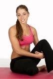 Junge Frau, die Fahrwerkbein an der Gymnastik umarmt Stockfotos