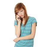 Junge Frau, die falsche Nachrichten durch Telefon erhält Stockfotografie