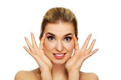 Junge Frau, die Falten auf ihrer Stirn überprüft lizenzfreie stockfotografie