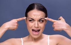 Junge Frau, die Falten auf ihrer Stirn überprüft stockfotografie