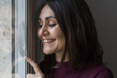 Junge Frau, die am Fenster lächelt Lizenzfreies Stockbild
