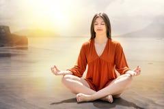 Junge Frau, die am Flussufer meditiert Lizenzfreie Stockfotos