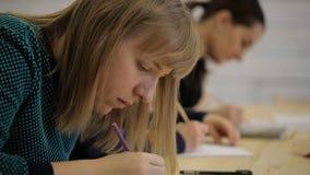 Junge Frau, die in Folge mit anderen auf Klassenzimmer für das Zeichnen sitzt stock footage
