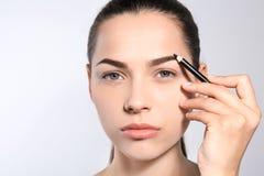 Junge Frau, die Form der Augenbraue mit Bleistift korrigiert stockbild