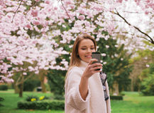 Junge Frau, die Fotos des Frühlingsblütengartens macht Stockfotografie