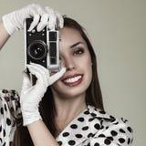 Junge Frau, die Fotos mit Weinlesefilmkamera macht Lizenzfreies Stockfoto