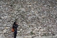 JUNGE FRAU, DIE FOTOS, STEINwand-HINTERGRUND MACHT stockfoto
