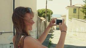 Junge Frau, die Fotos von der alten Mittelmeerstadtstraße mit ihrem Smartphone macht Stockbild