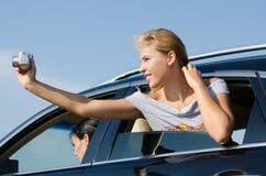 Junge Frau, die Fotos von einem Auto nimmt Stockbilder
