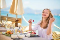 Junge Frau, die Früchte in einem Strandrestaurant isst Stockfotografie