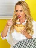 Junge Frau, die Frühstückskost aus Getreide isst Stockfotografie