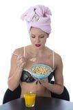 Junge Frau, die Frühstückskost aus Getreide nach Dusche isst Stockfotos