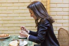 Junge Frau, die frühstückt Lizenzfreie Stockbilder