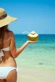 Frau, die frische Kokosnuss am tropischen Strand hält Stockbild