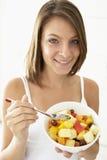 Junge Frau, die frischen Fruchtsalat isst Lizenzfreies Stockfoto